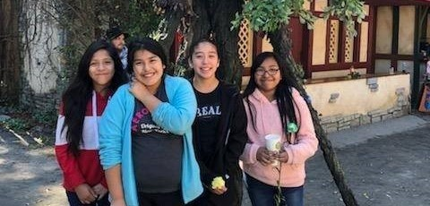 four 6th Graders pose in front of a house for a photo on their field trip to the Renaissance Festival.