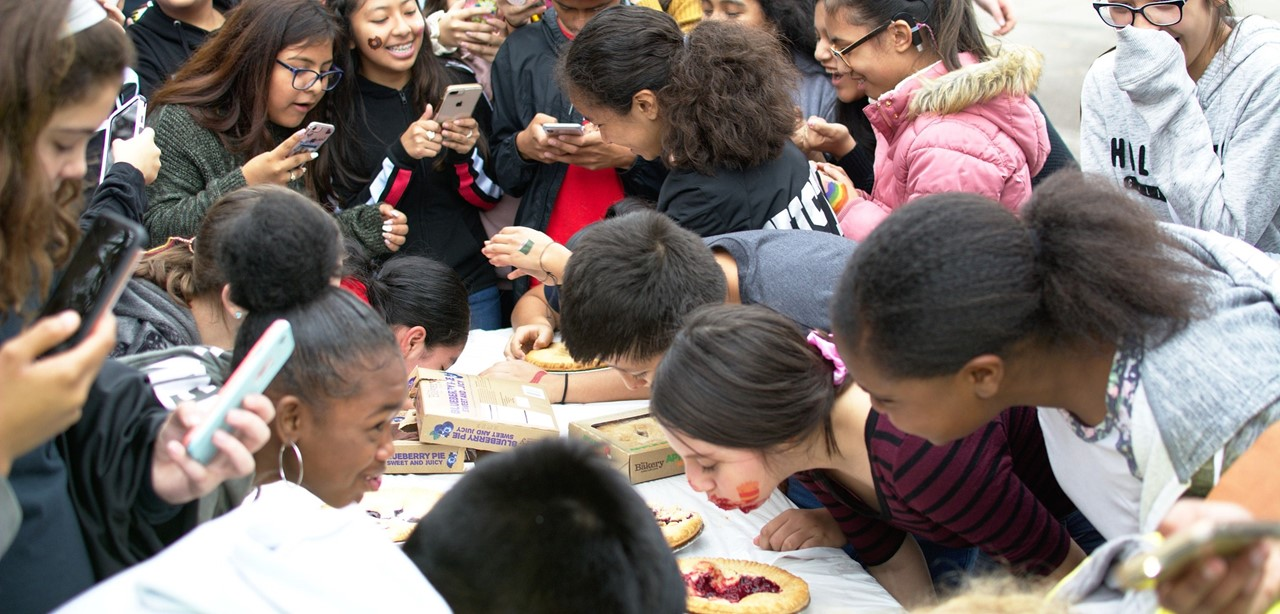 Students gathered around taking pictures of the pie eating contest