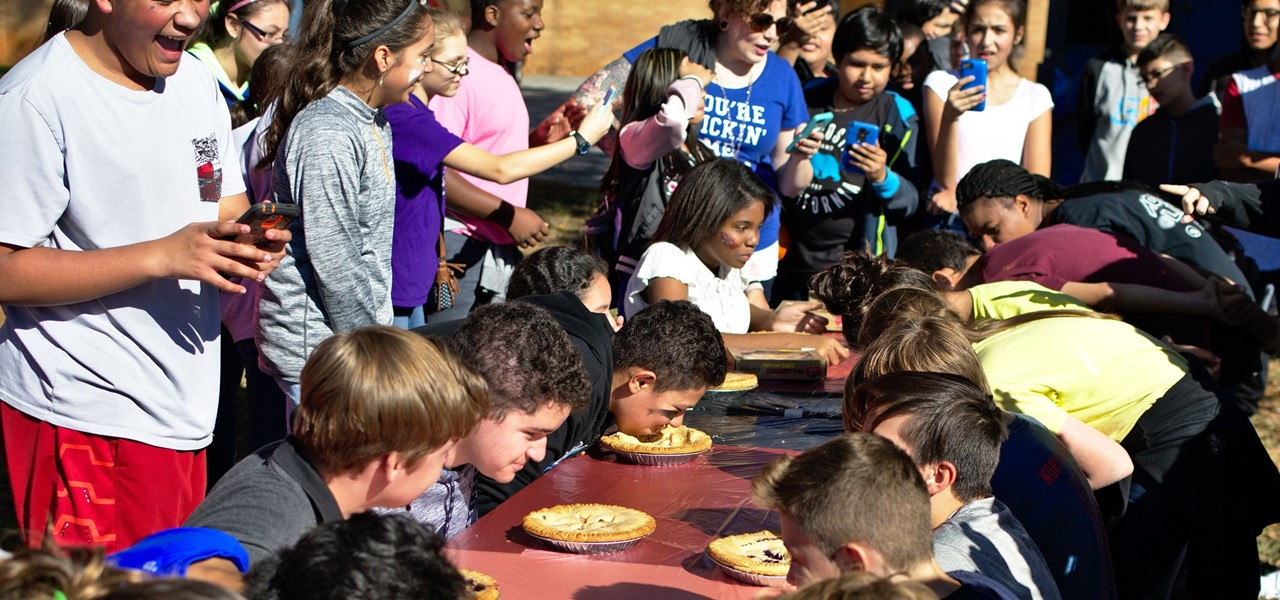 Students excitedly look on as other students engage in a pie eating contest.