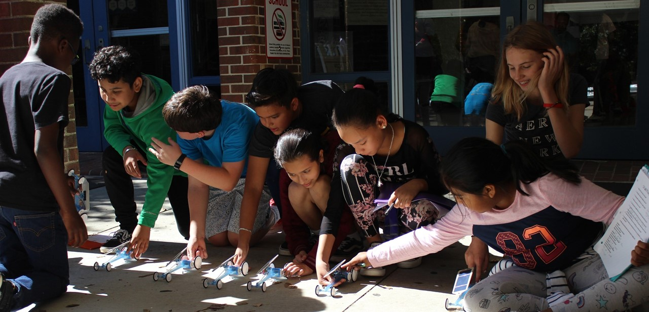 8 students line up solar powered cars to race down the sidewalk at the front walkway of NAMS,