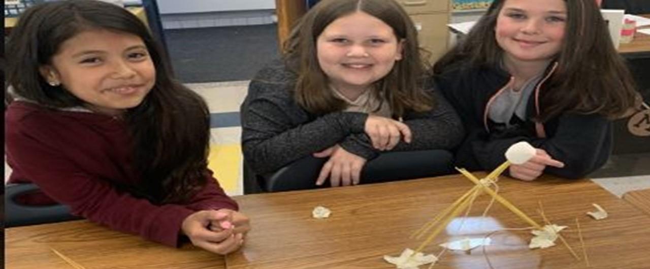 Three fifth grade girls display STEAM challenge the winning tallest spaghetti tower