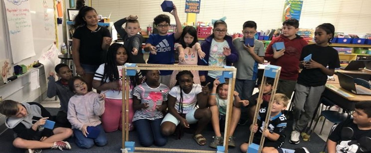 Fourth grade class on carpet displaying a model of a hundred thousand in math class