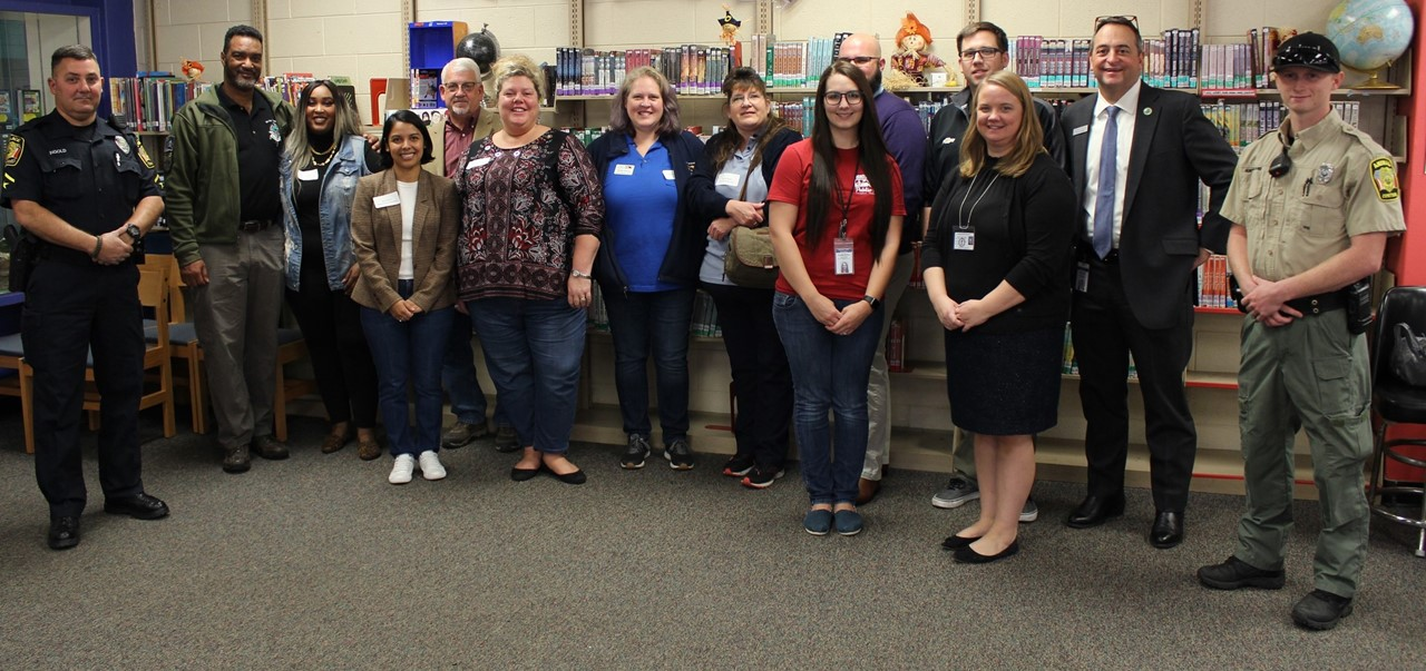 14 adults from the community who came in to speak for career day pose in from of a book shelf in the NAMS Media Center