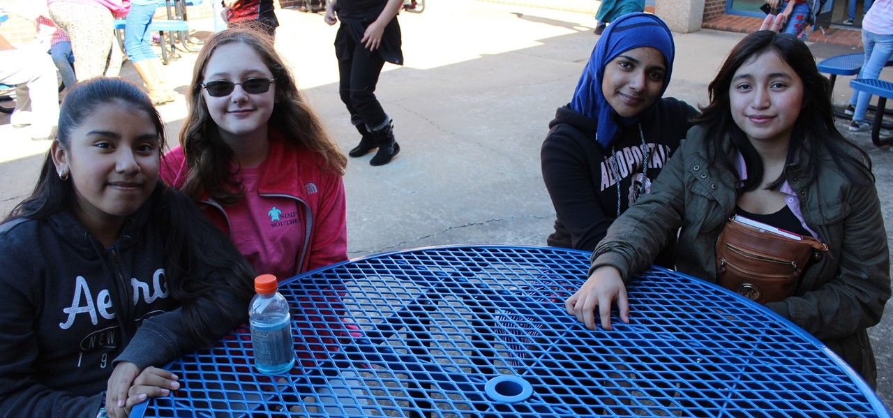 Four girls sit outside at a round, blue picnic table and smile at the camera while other students walk in the background.