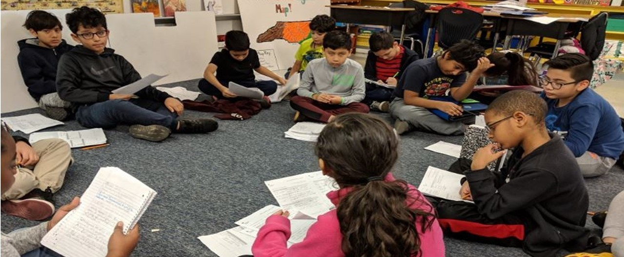 A group of Grade 4 students sitting on floor in a circle having a science talk