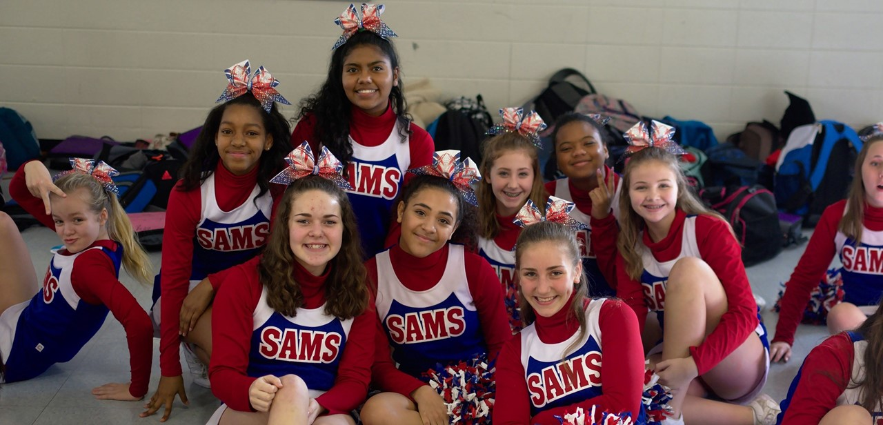 Cheerleaders sit and pose for picture
