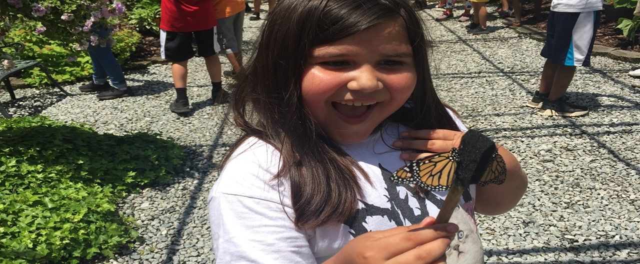 2nd grade student holding butterfly at All A Flutter Butterfly Farm