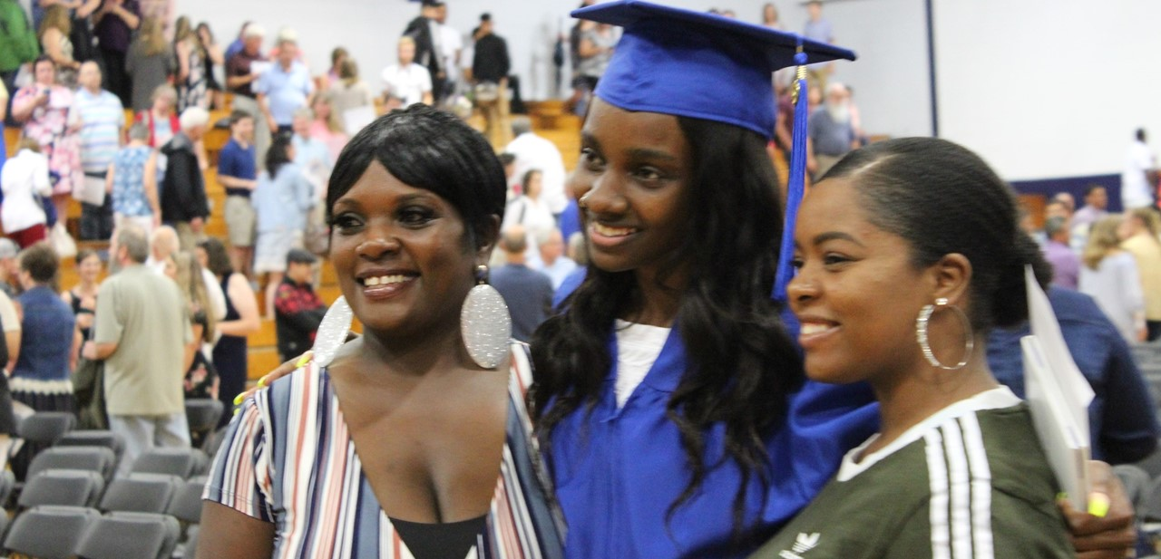 Graduating senior stands with her family after commencement.