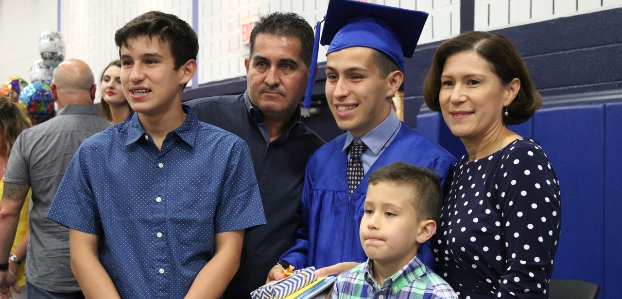 Alvis Adames stands with his family after graduation.