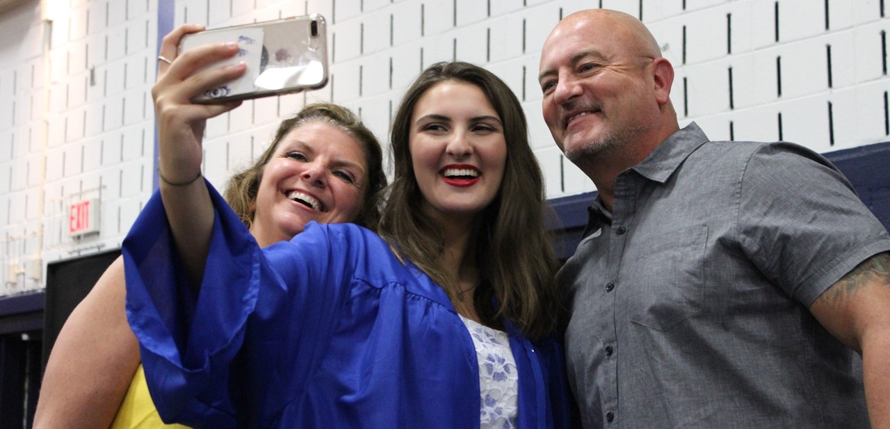 Graduating senior takes a selfie with her parents after commencement.