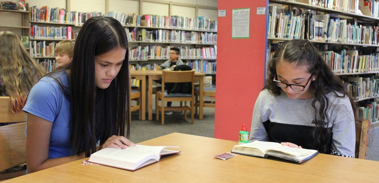 Two students are  sitting at a table, each reading their own book, in the media center.  There are two students in the background, also reading, and one student in the far background at another table who is also reading.
