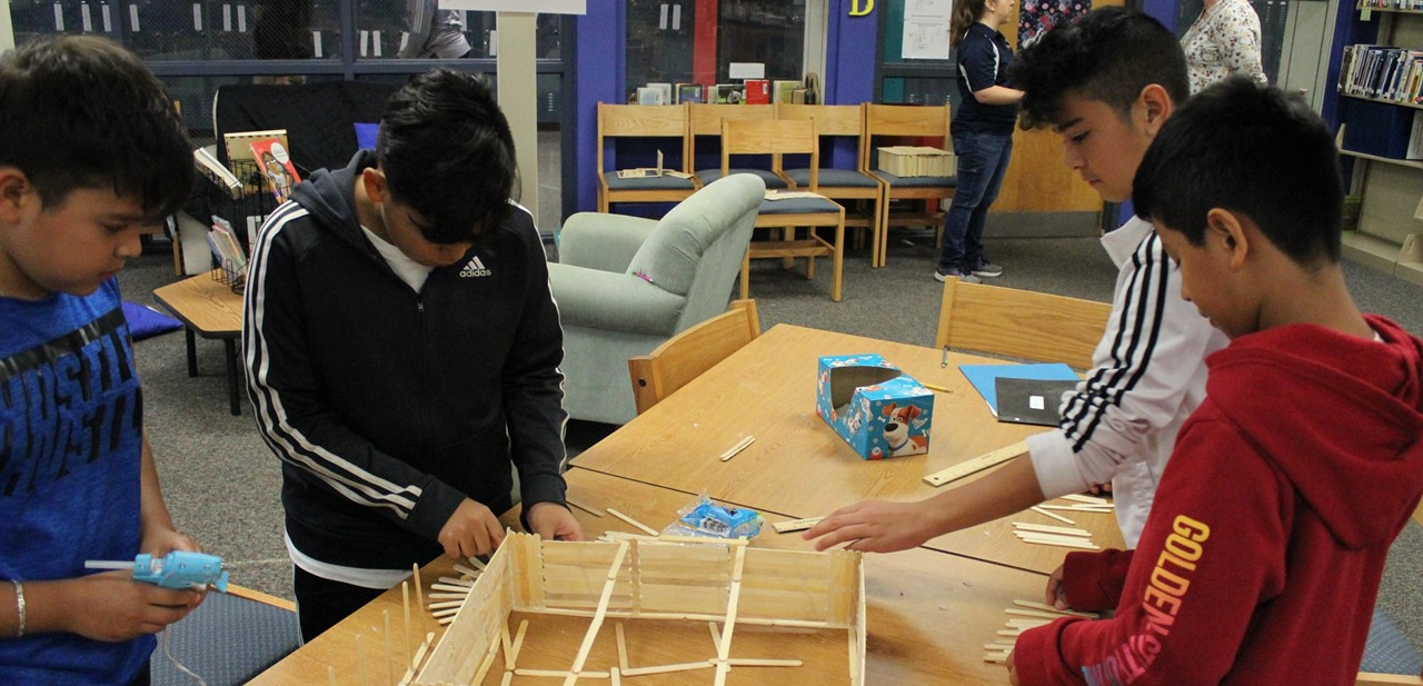 Four students work together in a group at at table in the media center to build a structure out of Popsicle sticks.