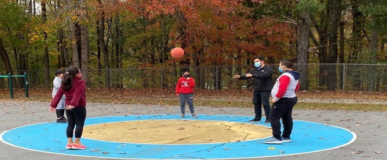 four fourth grade students and teacher playing ball outside on the blacktop