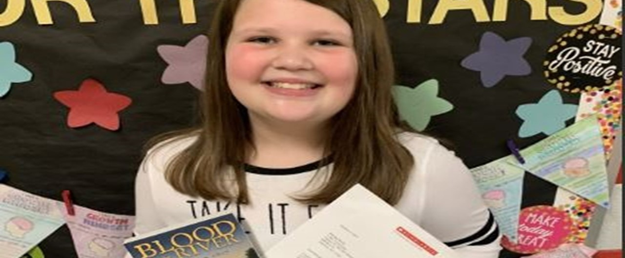 Fifth grade girl wins national Scholastic Storyworks writing contest.  Holding book and letter.