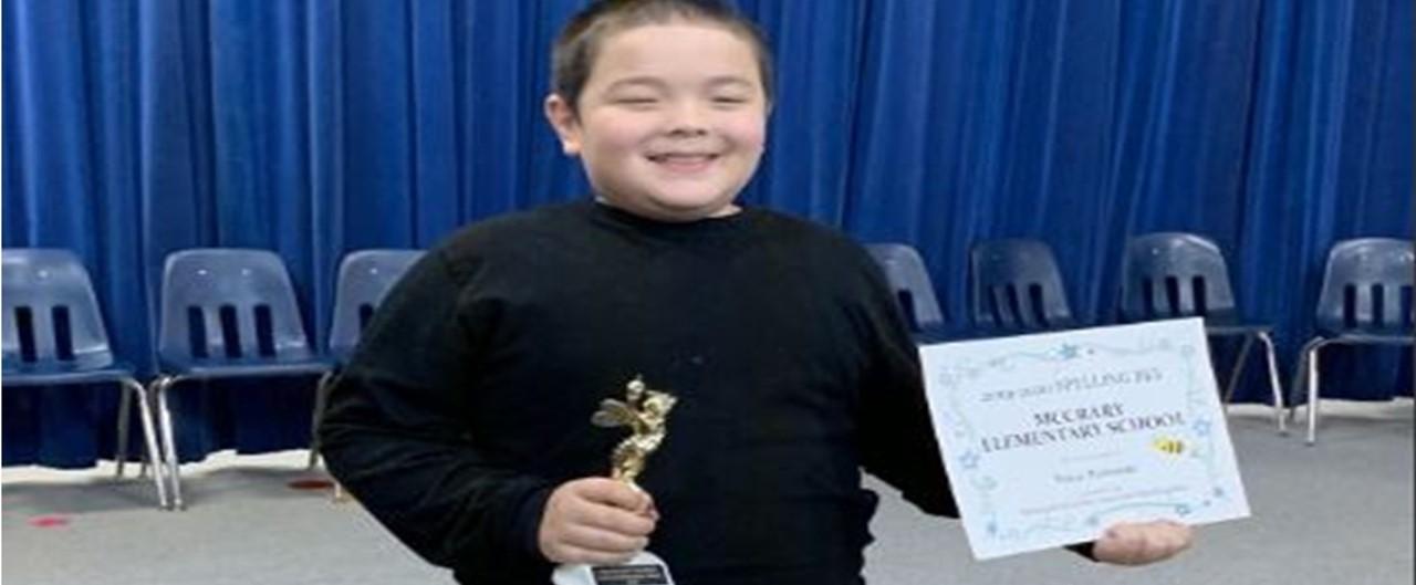 Fifth grade boy wins school spelling bee.  Holding certificate and trophy.