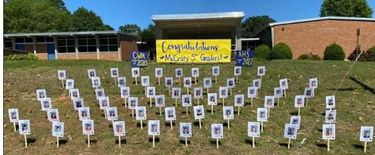 Fifth grade student photos displayed on posts in the yard in the front of school to celebrate graduation