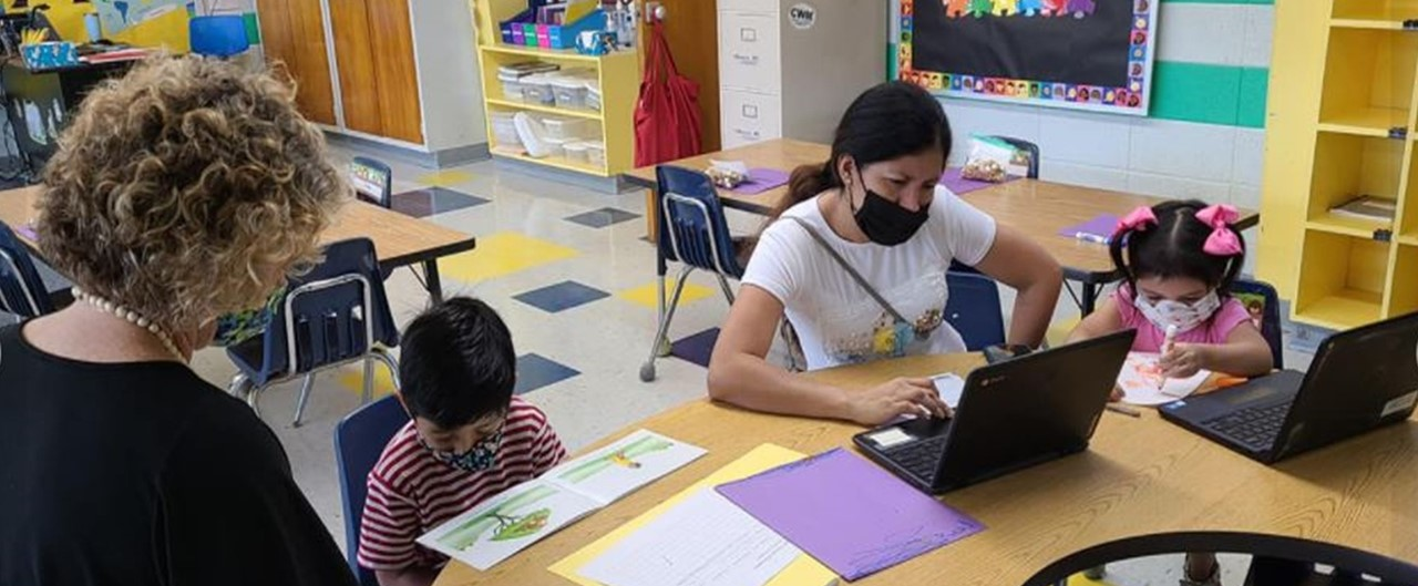 a first grade teacher, two students and a parent sitting at a table.  Looking at a book and using a computer